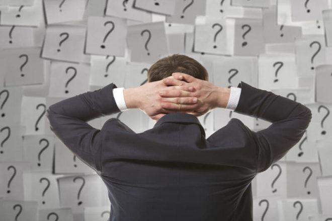 Foto zeigt einen Mann vor einer Wand mit Zetteln voller Fragezeichen