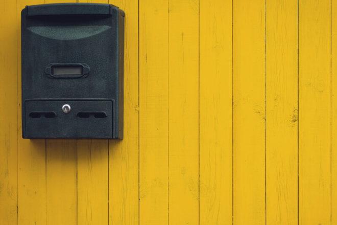Foto mit einem an der Wand hängenden Briefkasten, in dem kein Brief verloren gehen kann