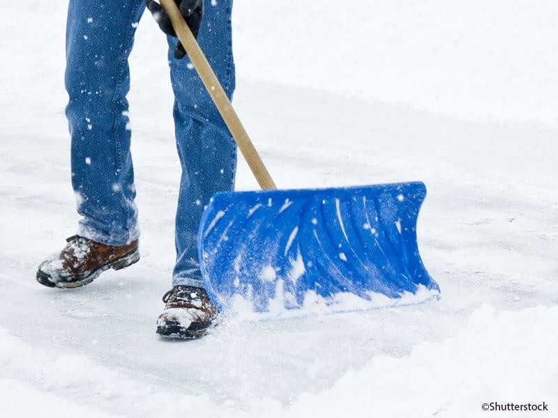 Foto von einem Mann der mit Schneeschaufel die Straße freiräumt