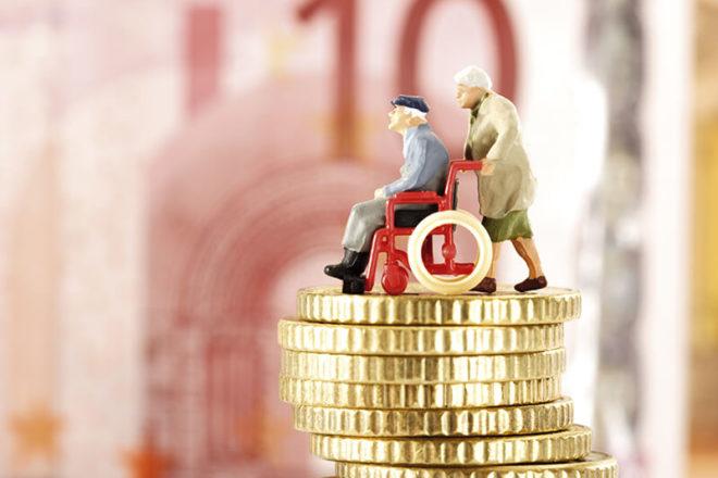 Foto zeigt Plastikfiguren von Rollstuhlfahrer und Betreuer auf einer Geldsäule als symbol für außergewöhnliche Belastungen