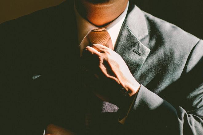 Bild von Mann der seinen Schlips bindet und überlöegt, ob er Berufsbekleidung absetzen kann