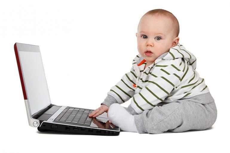 Baby sitzt vor einem Laptop.