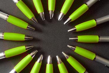 Kugelschreiber mit Werbelogo loegen auf dem Tisch und bilden eine Sonne