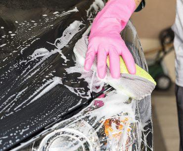 Minijobber reinigt ein Auto mit Wasser und Seife