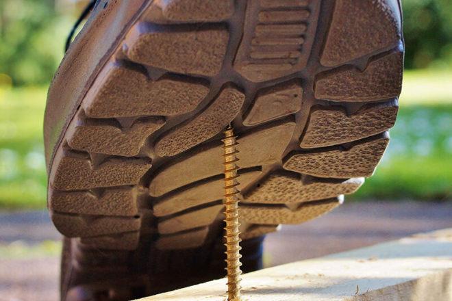 Foto von Bauarbeiter mit groben Schuhen der in eine Schraube tritt