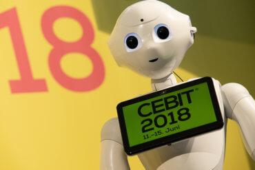 Bild von Roboter mit der Aufschrift Cebit 2018 auf einem Display vor seiner Brust