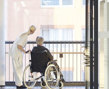 Bild mit Rollstuhlfahrer im Krankenhaus und seinem Betreuer