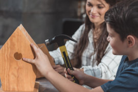 Mitarbeiter eines sozial engagierten Unternehmens baut mit einem Kind ein Vogelhaus