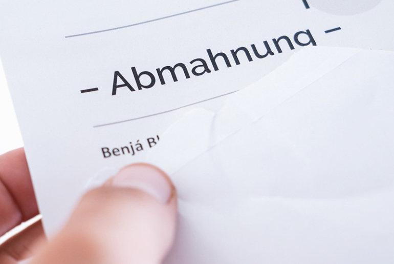 Unternehmer zieht Abmahnschreiben aus einem Umschlag