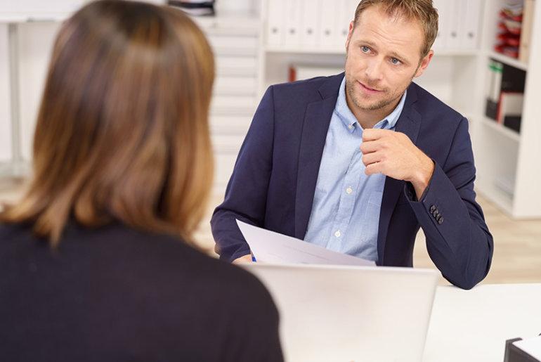 Vorgesetzter und Mitarbeiterin sitzen in einem Mitarbeitergespräch