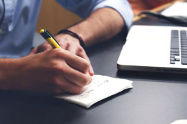 Foto von Unternehmer der schreibend am Schreibtisch sitzt