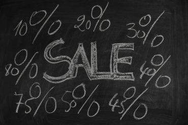 Bild Auf eine schwarze Tafel sind mit Kreide des Wort Sale und viele Prozentzeichen und Zahlen geschrieben