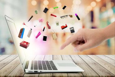 Foto von einem offenen Laptop aus dessen Bildschirm eingekaufte Waren in den Raum fliegen