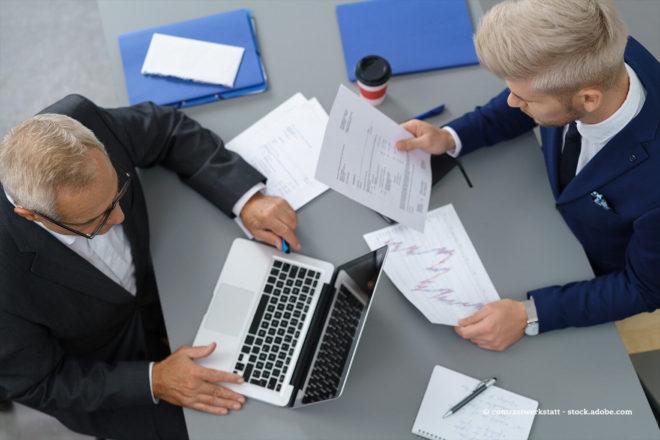 Seniorchef und Juniorchef gehen geschäftliche Details miteinander durch.
