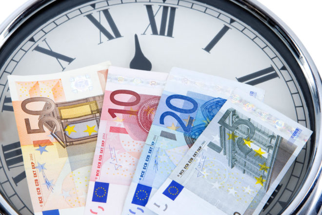 Geldscheine vor einer Uhr zeigen an, dass bei Zeitverzug ein Zuschlag anfallen könnte - was er einem aktuellen Urteil zufolge nicht tut.