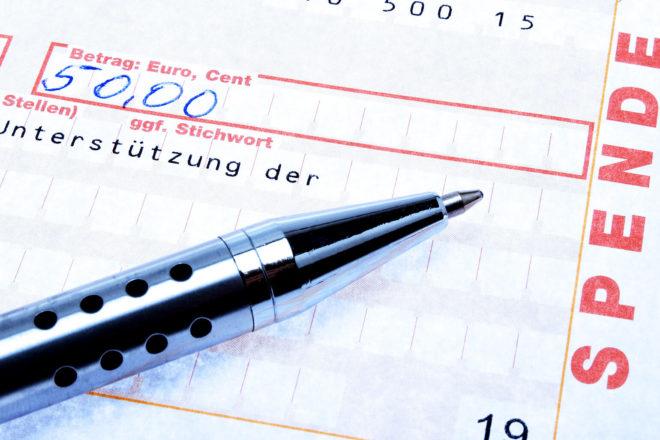 Überweisungsträger und Stift symbolisieren das Ansetzen von Sonderausgaben
