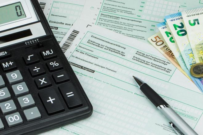 Taschenrechner und Kugelschreiber auf Steuerformular Anlage K für Kapitaleinkünftesteuererklärung. Bei der Steuer sollte auch die Erhöhung der Eigenkapitalquote bedacht werden