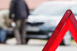 Autofahrer betrachtet den Unfallschaden und im Vordergrund steht ein Warndreieck