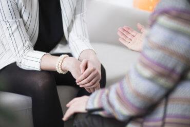 Bild zeigt die Händen von zwei sich gegenüber sitzenden Personen die sich unterhalten