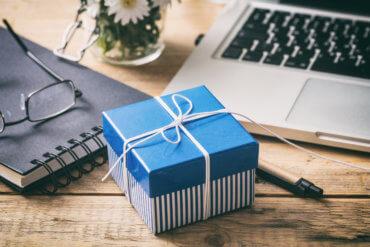 Foto mit kleiner Geschenkbox auf dem Schreibtisch neben dem Laptop