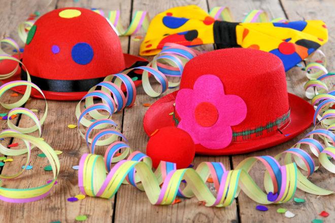 Bild mit Luftschlangen, Konfetti und Karnevalshüten symbolisiert Karneval und Fasching