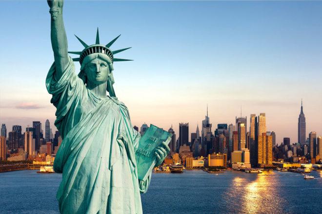 Die Freiheitsstatue vor der glitzernden See und Skyline New Yorks