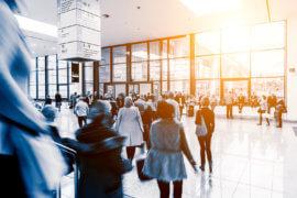 Foto zeigt Besucher im Eingangsbereiche iner Messehalle