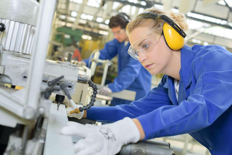 Mädchen mit Schutzausrüstung an einer Konstruktionsmaschine im Hintergrund ein Junge an einer ähnlichen Maschine