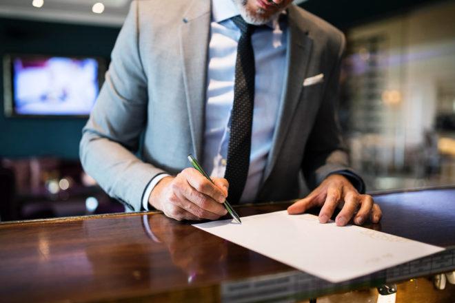 Mann im Anzug unterschreibt Anmeldung an der Hotelrezeption auf einer seiner Geschäftsreisen