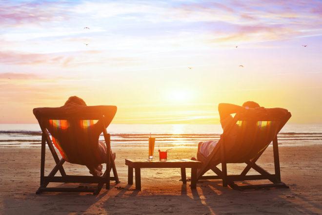 Zwei Urlauber im Liefestuhl am Szrand geniessen den Sonnenuntergang