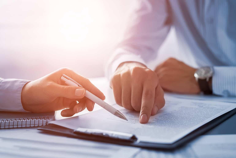 Die Hände zweier Personen zeigen etwas in Finanzunterlagen