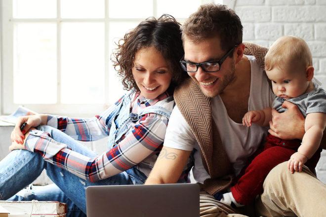 Bild zeigt junges Paar mit Baby vor einem Laptop, das Elterngeld für Selbständige bekommen würde