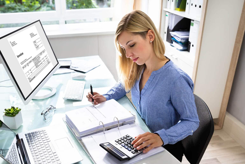 Frau bearbeitet Buchhaltungsunterlagen mit Taschenrechner vor dem Computer
