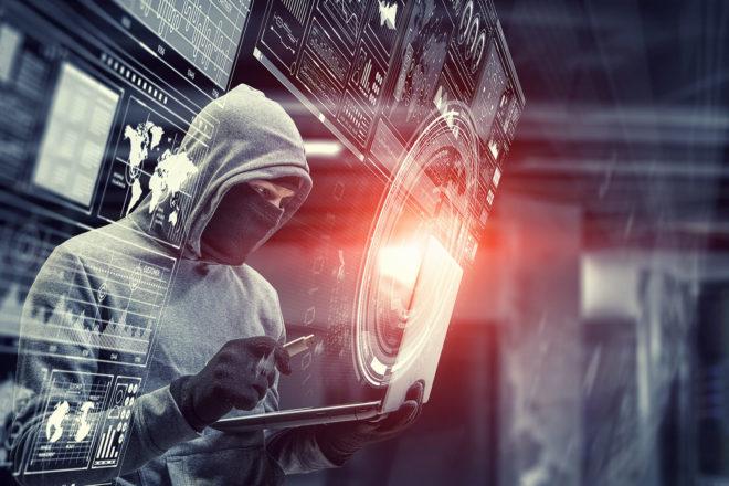 Foto von vermummtem Hacker der sich in einem Bildschirm spiegelt