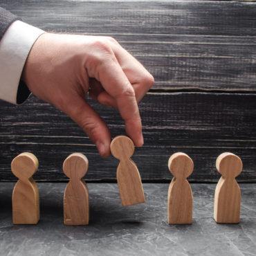 Hand wählt aus mehreren Holzfiguren eine aus