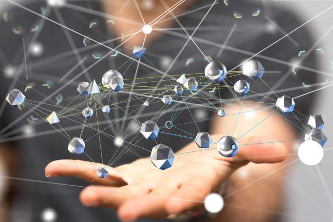 Foto einer Hand die Edelsetine hochwicrft die sich in einem Netzwerk verbinden