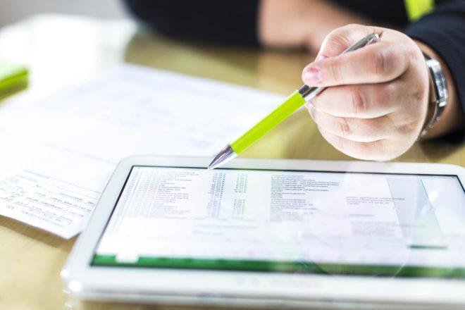 Bild zeigt Unternehmer, der Daten an seinem Tablet prüft und dann eine Rechnung schreiben will