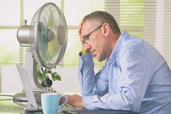 Schwitzender Mann sitzt vor Bildschirm und hofft in der Hitze auf Kühlung durch Ventilator