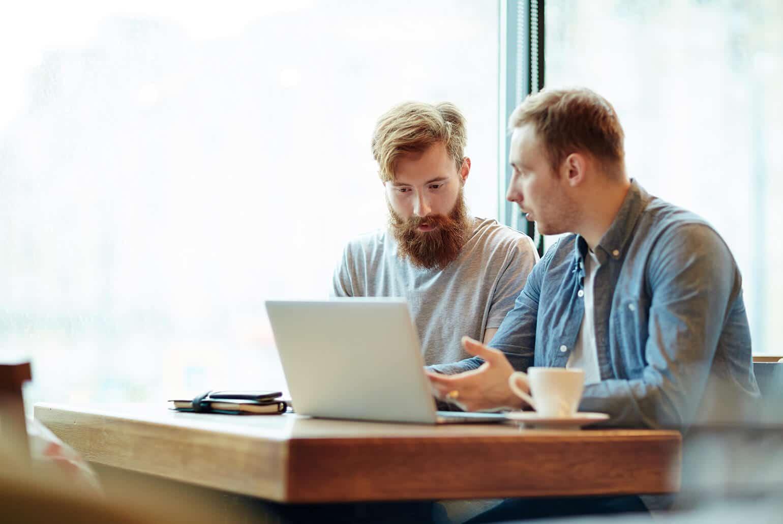 Zwei junge Männer sitzen gemeinsam am Laptop und besprechen etwas.