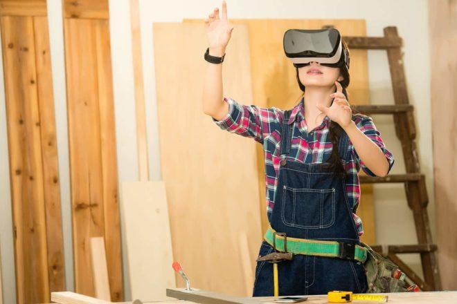 Schreinerin sieht sich Positionierung eines Schranks mit VR-Brille an