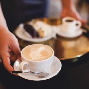 Foto von einem Gastronomiemitarbeiter der Kaffee und Kuchen serviert