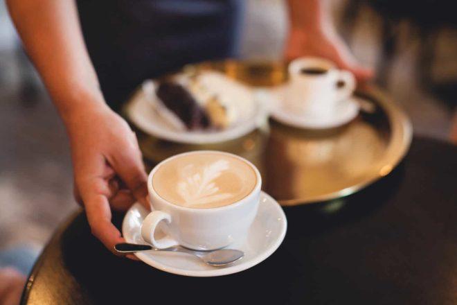 Foto von einem Gastronomiemitarbeiter der Kaffee und Kuchen serviert. In der Gastronomie arbeiten viele mit einem Minijob auf Abruf