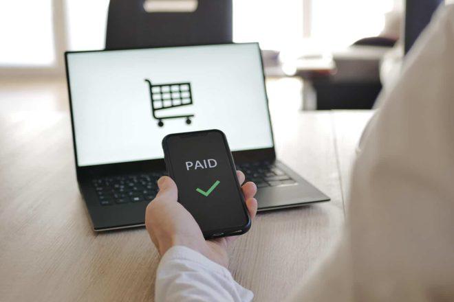 Mann sitzt mit Smartphone in der Hand vor Laptop mit Symbol für Einkaufswagen und bezahlt online