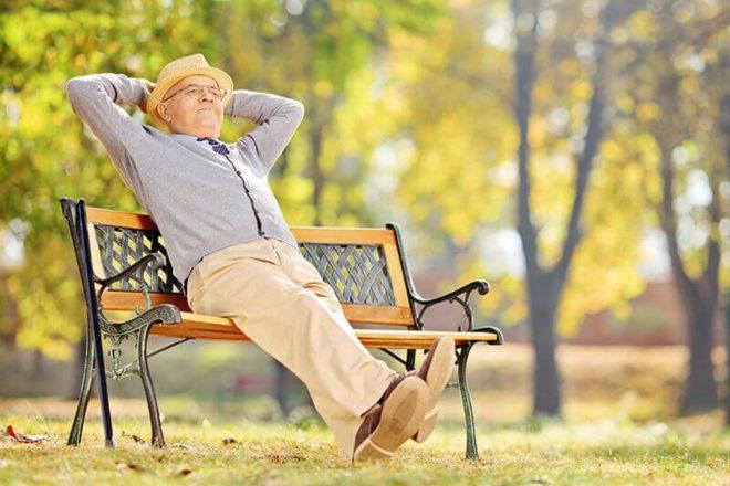 Zufriedener älterer Herr sitzt mit hinter dem Kopf verschränkten Armen auf einer Parkbank im Grünen