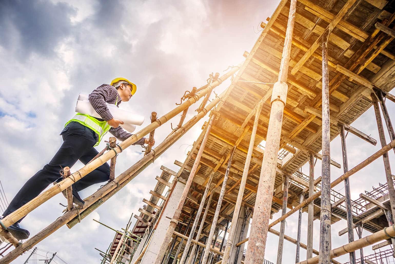 Bauarbeiter klettert auf ein sonnenbeschienenes Baugerüst