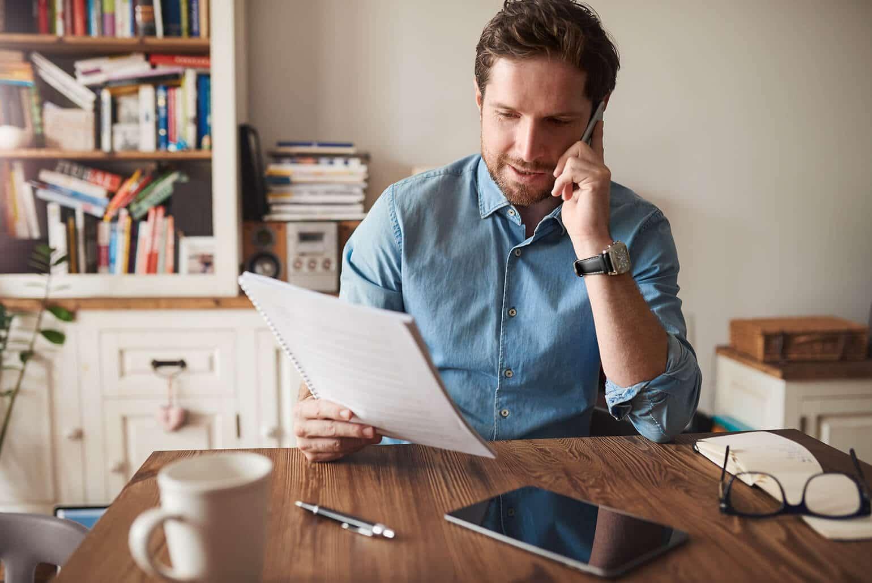 Mann sitzt im Homeoffice am Tisch und telefoniert mit Blick auf ein paar berufliche Unterlagen