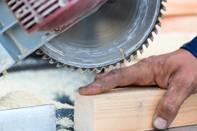 Foto von Schreiner dessen Hand beim Arbeiten in eine Säge kommt