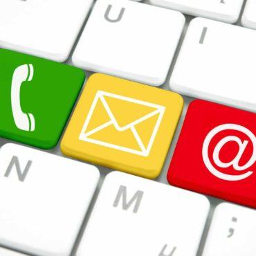 Bild von Computertastatur mit den Symbolen von Telefon, E-Mail und Internet