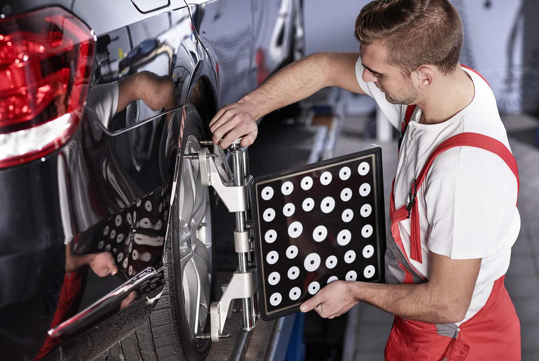 Foto mit einem Handwerker der neue Reifen auf einem Auto montiert