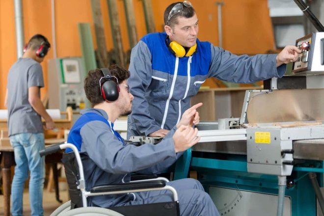 Mitarbeiter mit und ohne Rollstuhl an einer Maschine in einem Social Business